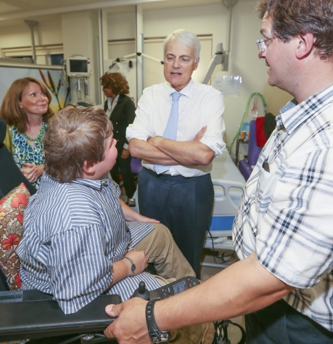 Image shows Sir Robert Francis who opened  the  centre, talking  with staff and a patient.