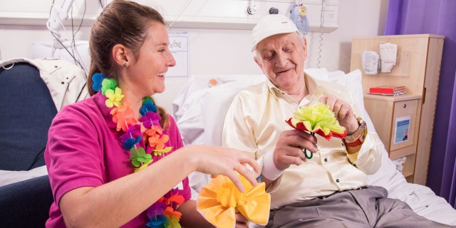 A volunteer making paper flowers with a patient
