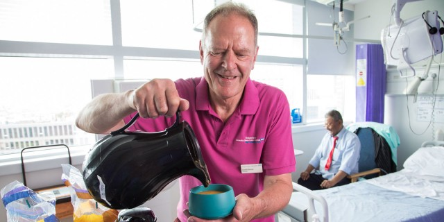 A volunteer serving soup at lunchtime